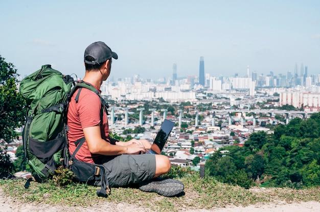 Uomo nomade digitale che viaggia per il mondo lavorando Foto Premium