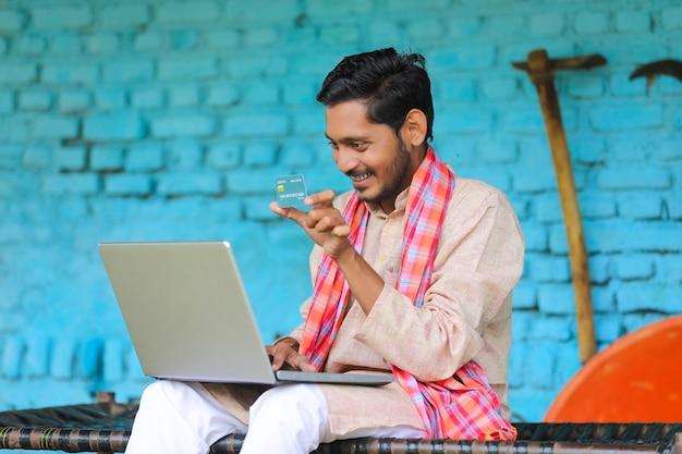 Concetto di pagamento digitale: agricoltore indiano che utilizza laptop e carta a casa