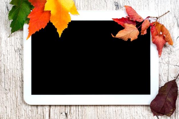Schermo vuoto del nero della compressa di digital con le foglie di autunno variopinte sulle plance di legno bianche