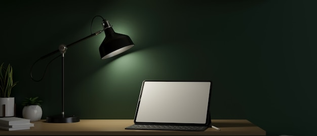 Computer tablet digitale in mockup schermo vuoto in condizioni di scarsa illuminazione dalla lampada da tavolo ufficio di lavoro scuro