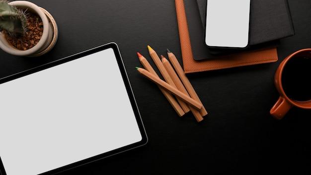 Mockup di tablet digitale e mockup di smartphone con accessori in vista dall'alto di colore nero e arancione