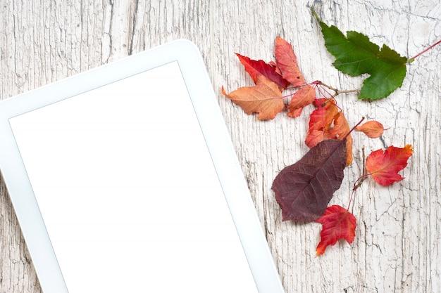 Schermo vuoto bianco della compressa di digital con le foglie di autunno variopinte sulle plance di legno bianche