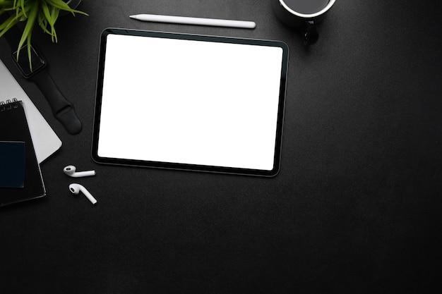 Tablet digitale con schermo vuoto, penna stilografica, auricolare wireless e spazio copia sul tavolo scuro.