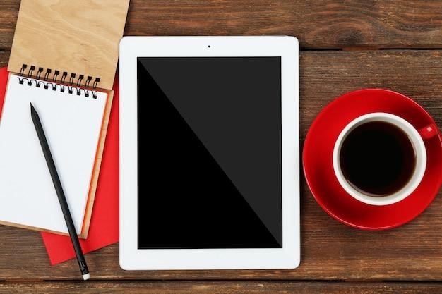 Tavoletta digitale con tazza di caffè e notebook su tavolo di legno, primo piano