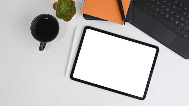 Tavoletta digitale con schermo vuoto, tazza di caffè, taccuino e penna stilo sulla scrivania bianca.