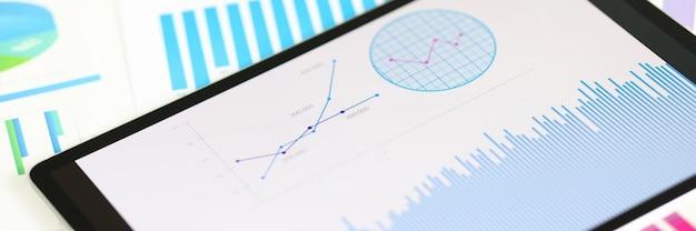 Tavoletta digitale con grafici e tabelle che si trovano sul concetto di statistiche aziendali del primo piano dei documenti