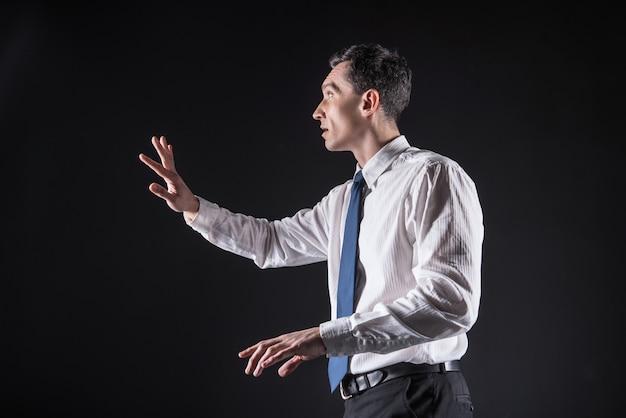 Tecnologia digitale. piacevole simpatico bell'uomo in piedi davanti al grande schermo sensoriale e toccandolo mentre si utilizza la tecnologia digitale