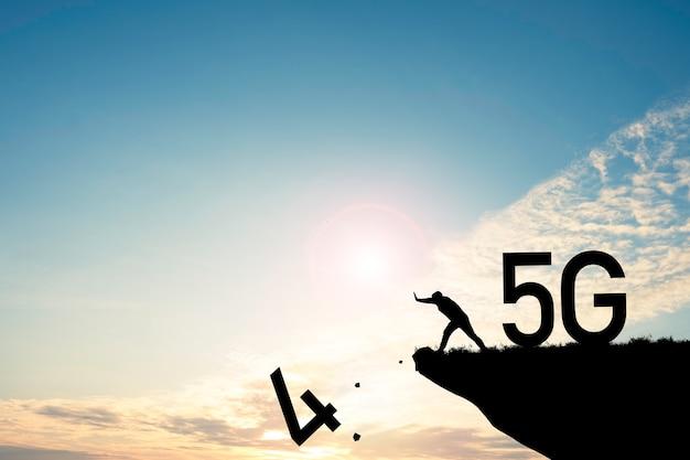 Concetto di trasformazione digitale e tecnologica. l'uomo spinge il numero quattro dalla scogliera per cambiare la tecnologia da 4g a 5g.