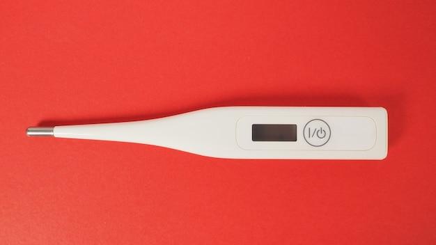 Termometro digitale su sfondo rosso.