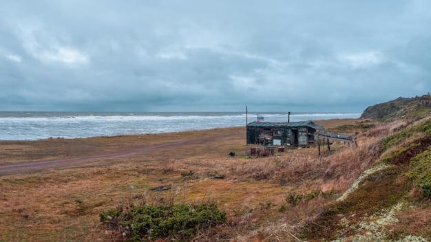 Una vecchia casetta di pescatori fatiscente in un autentico villaggio sulle rive del mar bianco. penisola di kola. russia.