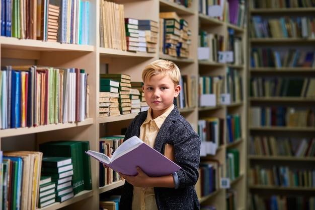 Ragazzo bambino diligente con il libro tra gli scaffali nella biblioteca del campus, sta guardando la fotocamera. apprendimento, cervello, concetto di educazione