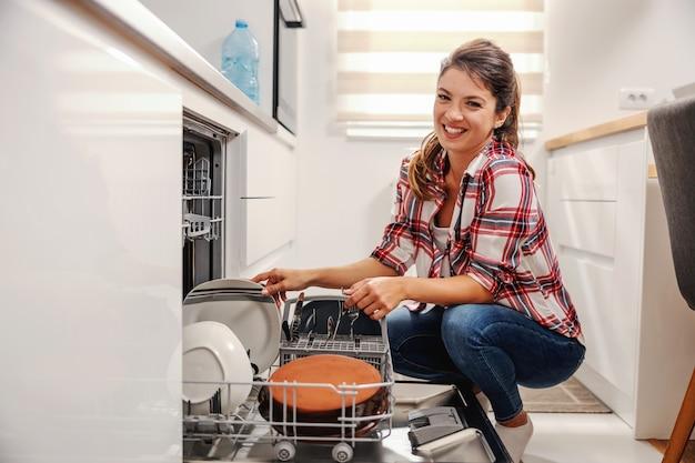 Casalinga diligente che mette i piatti in lavastoviglie.