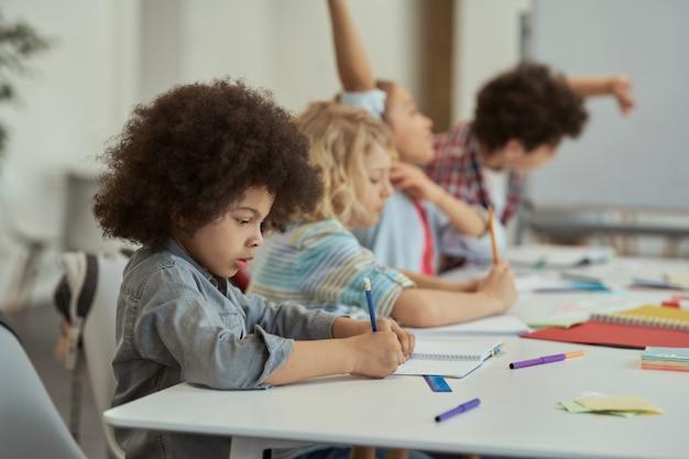 Piccolo scolaro diligente che scrive sul suo quaderno mentre studia seduto al tavolo alle elementari