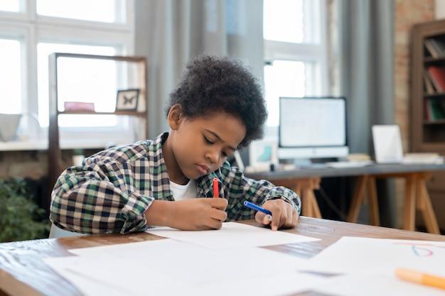 Scolaro diligente in abbigliamento casual che disegna con evidenziatori su carta da tavolo in soggiorno mentre si gode il tempo libero dopo aver fatto i compiti