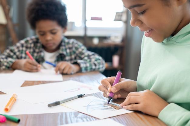 Studentessa diligente e suo fratello carino disegnano con evidenziatori su carta da tavolo in soggiorno mentre si godono il tempo libero dopo aver fatto i compiti