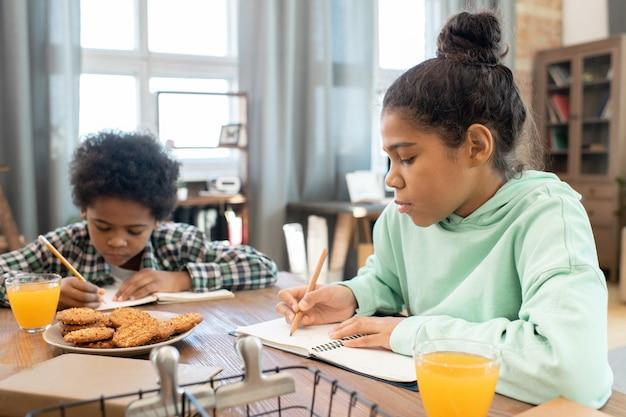 Studentessa diligente e suo fratello carino che prendono appunti nei quaderni da tavolo in soggiorno e fanno spuntini con succo d'arancia contro le finestre