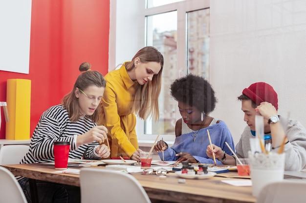 Studenti diligenti. tre diligenti studenti alla moda del dipartimento d'arte che lavorano duramente in classe