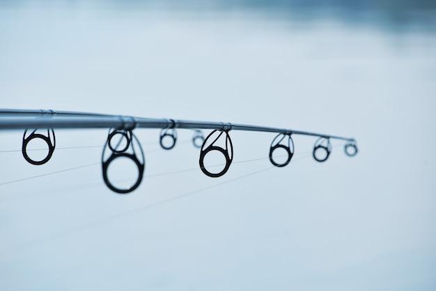 Diminuzione prospettiva di canne da pesca su sfondo blu acqua con copia spazio