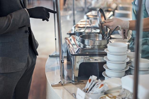 Cassiere della tavola calda che apre una pentola per zuppa per un cliente