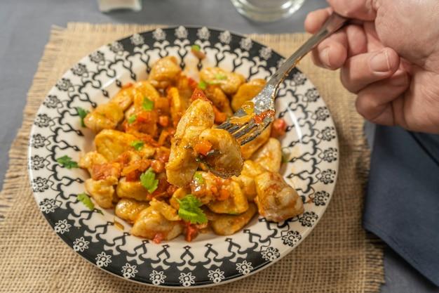 Diner prendendo con la sua forchetta alcuni gnocchi fatti in casa con salsa di pomodoro serviti su un piatto azzurro. cibo italiano.