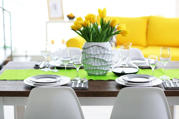 Interno sala da pranzo con divano e tavolo servito per cena