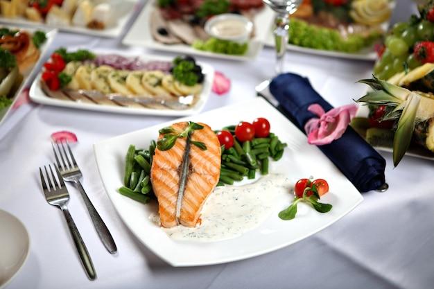 Tavolo da pranzo servito con vari snack e bistecca di salmone alla griglia su un piatto con fagiolini.