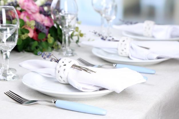 Regolazione del tavolo da pranzo con fiori di lavanda sul tavolo, primo piano. concetto di matrimonio di lavanda