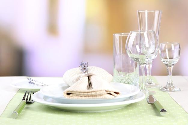 Regolazione del tavolo da pranzo con fiori di lavanda sul tavolo sul ristorante sfocato