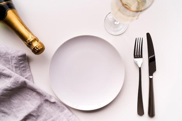 Tavolo da pranzo con il piatto vuoto e la bottiglia del champagne sopra fondo bianco