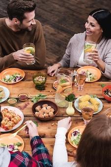 Cenare con gli amici. vista dall'alto di quattro persone che cenano insieme