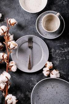 Impostazione del posto per la cena. un moderno piatto in ceramica blu con forchetta d'argento decorato con fiori di cotone su una superficie scura. vista dall'alto, piatto.