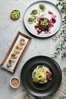 Vista dall'alto del tavolo da pranzo. set di cibo, piatto dell'albero con bistecca, pasta con spinaci e panini con salmone.