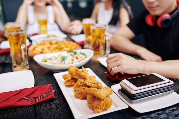 Tavolo da pranzo con cibo e telefoni cellulari