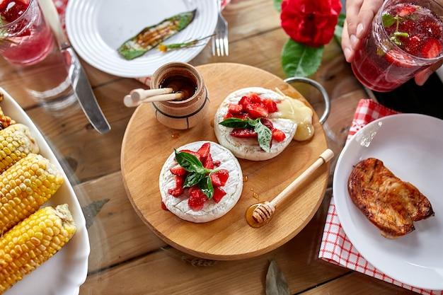 Tavolo da pranzo con grigliata di carne, camembert, verdure arrosto, salse e limonata, varietà di antipasti che servono sul tavolo all'aperto della festa.