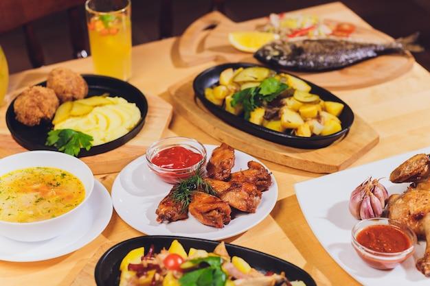 Tavolo da pranzo con grigliata di carne, patate novelle arrosto, verdure, insalate, salse, snack e limonata, vista dall'alto.