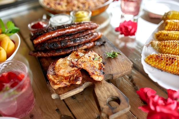 Tavolo da pranzo con grigliata di carne, verdure arrosto, salse e limonata, varietà di antipasti che servono sul tavolo all'aperto della festa
