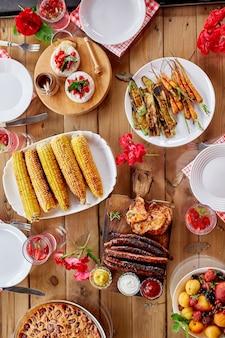Tavolo da pranzo con grigliata di carne, salsicce, mais, verdure arrosto, salse, snack e limonata, vista dall'alto, cena o pranzo in famiglia, concetto di cibo
