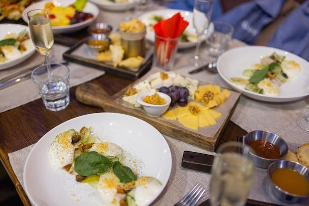 Tavolo da pranzo con snack decorato con bellissimi fiori estivi. tabella degli alimenti concetto di pasto biologico delizioso sano. aspettando l'ospite.