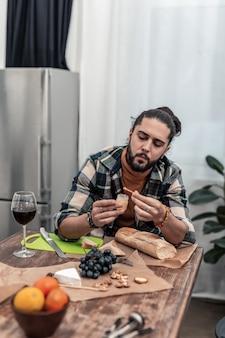 Ora di cena. un bell'uomo simpatico seduto in cucina mentre cena