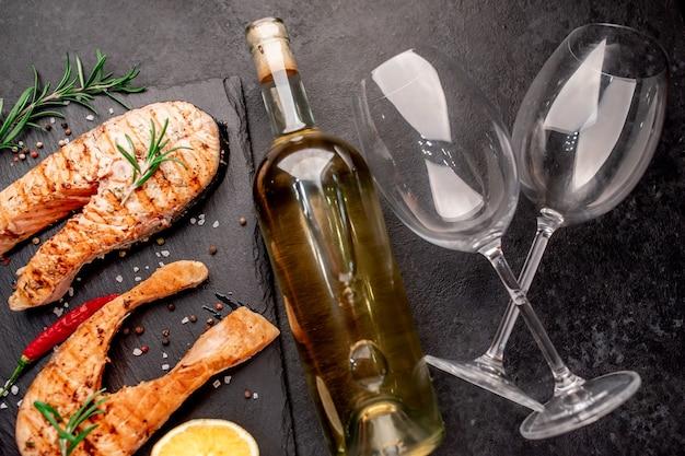 Cena per due bistecche di salmone alla griglia bottiglia di vino e bicchieri sul tavolo di pietra
