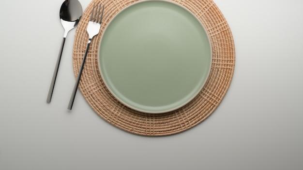 Tavolo da pranzo con piatto in ceramica turchese e argenteria su tovaglietta