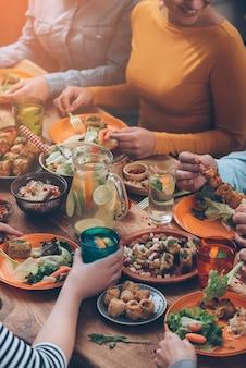 Pranzo insieme. vista dall'alto di un gruppo di persone che cenano insieme seduti al tavolo di legno rustico
