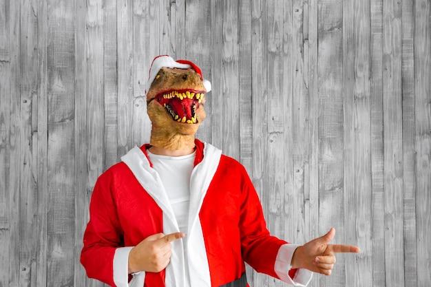 Dinosauro travestito da babbo natale che punta a destra con le mani.
