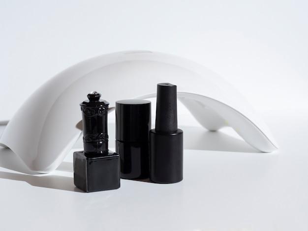 Una lampada a diodi per unghie e un set di smalto cosmetico su sfondo bianco. dispositivi per manicure e pedicure