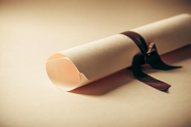 Diploma legato con nastro marrone beige su sfondo
