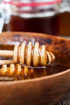 Immerso nel miele appositamente realizzato in legno, cucchiaio grossolano fatto in casa, miele d'api dolce e cucchiaio di legno che consente di trasferire e versare il miele senza sgocciolare e spalmare