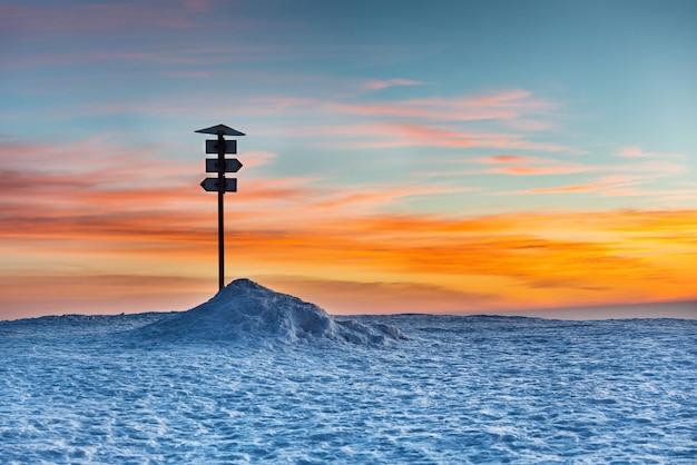 Segnale di direzione sulla cima della montagna invernale contro il tramonto
