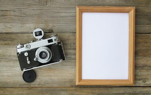 Direttamente sopra l'inquadratura di una cornice vuota con una fotocamera retrò su un vecchio tavolo di legno.