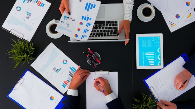 Direttamente sopra l'inquadratura di uomini d'affari seduti alla scrivania dell'ufficio che discutono di documenti finanziari utilizzando dispositivi digitali