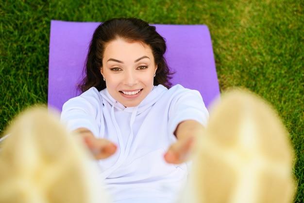 Direttamente sopra il colpo di bella ragazza sdraiata su un tappetino sportivo viola, fare esercizi addominali, scricchiolii e trazioni e guardare nella fotocamera